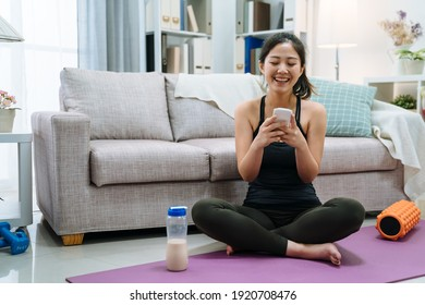 fit female athlete relax after training sit in sport yoga mat drinking from milk bottle. happy woman enjoy using mobile phone text message and resting after fitness workout. smiling girl on floor.