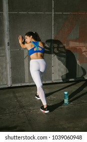 Fit female athlete stretching legs for warming up before urban running workout. Fitness young woman exercising outside.
