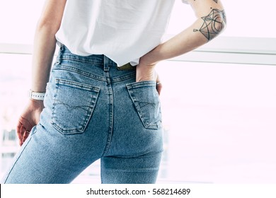Fit female butt in jeans. Hand with tattoos in pocket