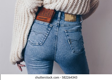 Fit female butt in jeans with passport in pocket and oversized sweater