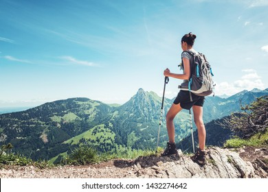 Fit female hiker with backpack and poles standing on a rocky mountain ridge looking out of green alpine valleys and peaks in a healthy outdoors lifestyle concept