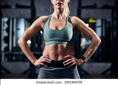 Fit female placing her hands on a waist and standing with a straight back