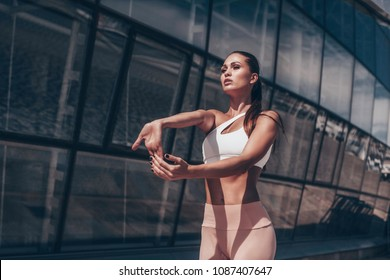 Fit female in sportswear exercising outdoors. Street workout.