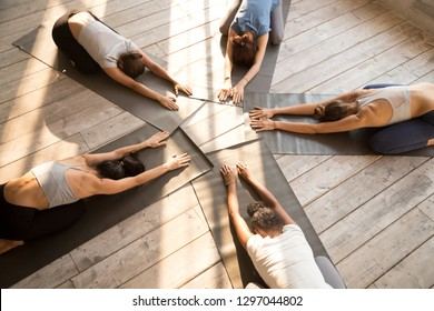 Fit female yogi stretch on rubber mats practicing yoga in fitness studio together, toned women relax in child pose lying on floor in circle, group of girls train doing pilates in gym. Wellness concept