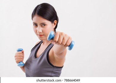 fit and firm woman punching, woman fitness training, fit girl weight training; strong fitness woman punching with dumbbell studio isolated; strong asian fitness girl delivers impact dumbbell punch