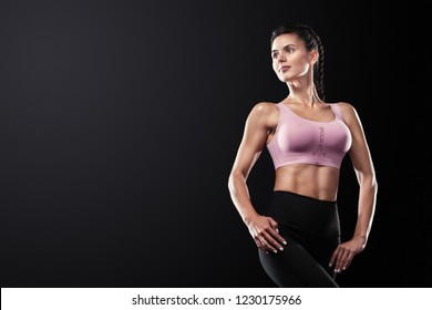 Fit fitness woman athlete posing on black background. Sport concept with copy space.