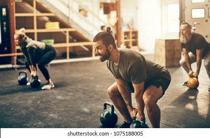 Fit and focused group of people in sportswear lifting dumbbells together during an exercise class at a gym