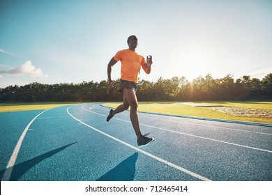 Fit and focused young African male athlete running alone along a race track while out training on a sunny day