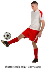Fit football player playing with ball on white background