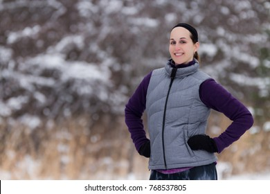 Fit girl in cold weather workout attire near forest during winter