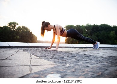 Fit girl doing plank exercise outdoor in the park warm summer day. Concept of endurance and motivation