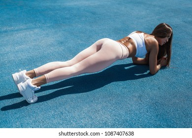 Fit Girl Doing Plank. Street Workout. Motivation concept.
