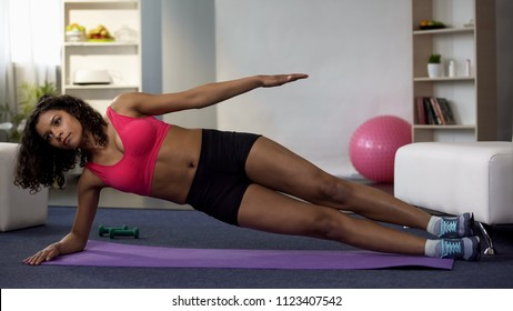 Fit girl doing side plank exercise, working out routine, building up muscles
