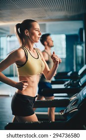 Fit girl with earphones running on treadmill in sports club