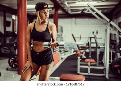 Fit girl exercise with dumbells in gym.