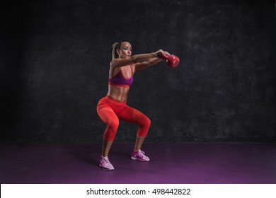 Fit girl exercise in the gym with kettle-bell.