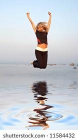 fit girl jumping at the seashore