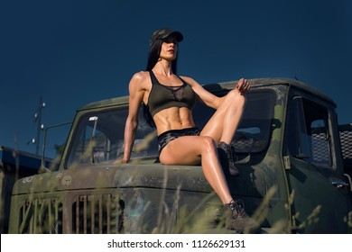 Fit girl in military wear on the hood of old army lorry truck