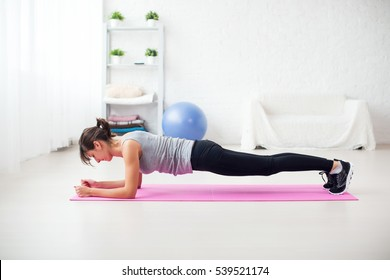 Fit girl in plank position on mat at home the living room exercise for back spine and posture Concept pilates fitness sport.