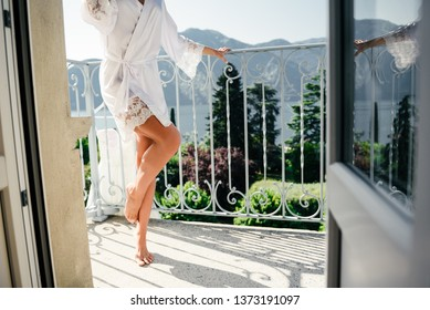a fit girl in a silk robe stands on the open balcony on a sunny day, a balcony is overlooking the mountains and the lake Como