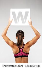 fit girl in sportswear holding the letter w