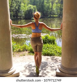 Fit girl standing between columns in the park. Outdoors fun, person surrounded by beautiful nature. Relax and free time summer or spring. Sporty outfit, snapshot of beautiful blonde woman.