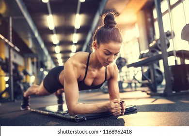 Fit girl training plank exercise in gym