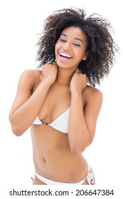 Fit girl in white bikini smiling at camera on white background