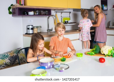 fit and good looking young mother is cooking together with youngest daughter,teaching her how to cook, ,while to other a little older kids sitting at the kitchen table and preparing vegetables