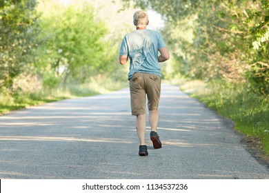 Fit grey haired mature male jogs on road, being photographed in motion, has physical exercises early in morning, wants to have healthy body, poses back to camera. Fitness and pensioners concept