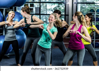 Fit group dancing and smiling in the gym