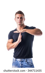 Fit handsome young man gesturing time out sign with his hands isolated on white background