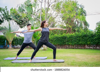 Fit happy people working out outdoor. Asian couple exercising together on a yoga mat at home garden. Family outdoors. exercise at the home concept and new normal.