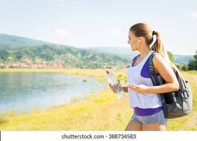 Fit happy young blonde Caucasian woman hiking in nature by the lake on sunny summer day. Girl with water bottle and backpack in nature walking and relaxing. Mild retouch, no filter, natural light