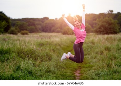 Fit happy young woman in sportwear jumping into air on path through meadow