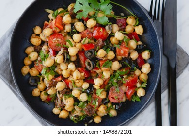 Fit and healthy beautifully colourful vegetarian chickpea salad with pepper, black oloves and tomatoes. Served in a dark plate.