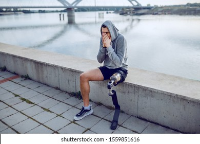Fit healthy caucasian handicapped sportsman with artificial leg and hoodie on head sitting on quay and resting.