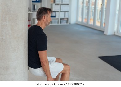 Fit healthy man doing a wall leg sit or squat in an office gym to strengthen and tone his muscles in an active lifestyle concept with copy space