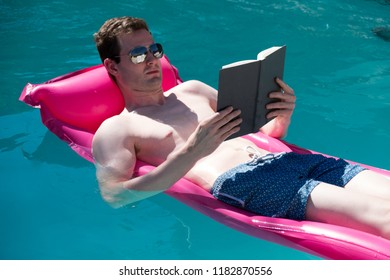 Fit and healthy man lounging in an outdoor swimming pool in blue swimming trunks on a bright pink raft reading a book in the pool in the summer on a sunny day. Relaxing in a backyard swimming pool.