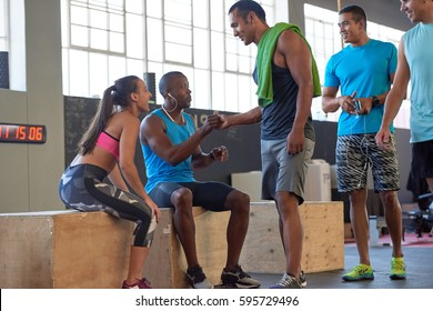 Fit healthy mixed race man greeting his friend in the gym before workout crossfit class