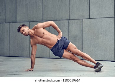 Fit healthy muscular young man with a bare chest doing side planks in an urban environment