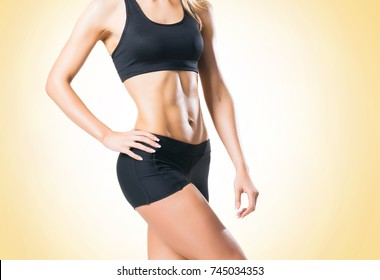 Fit, healthy and sporty woman in sportswear over yellow background.