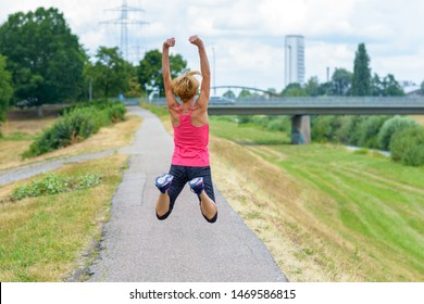 Fit healthy woman full of vitality leaping in the air with raised arms celebrating the freedom of the countryside