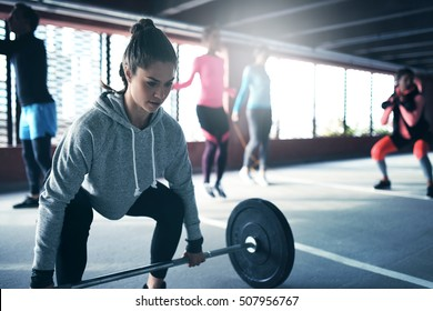 Fit healthy woman lifting a weight barbell from floor, exercising with group of people outside urban setting