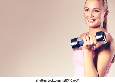 Fit and healthy woman smiling and holding a dumbbell to her shoulder. Image with copyspace for text