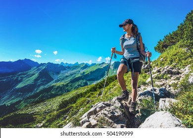 Fit healthy young woman trekking in the Alps standing on a rocky trail looking down at the camera with a smile, Grosser Daumen, Germany