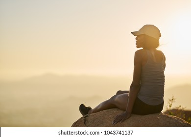 fit hiker resting on rock on top of mountain watching sunset