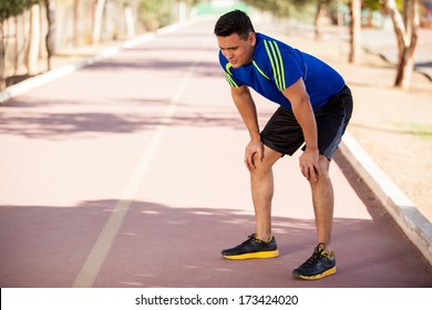 Fit Hispanic runner stopping for a moment to get some air after a long run