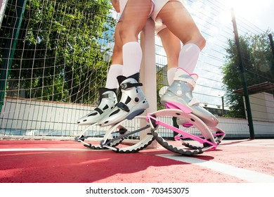 Fit legs in kangoo jumping shoes. Two sexy girls do sport kangoo exercises on pink background . Group fitness.