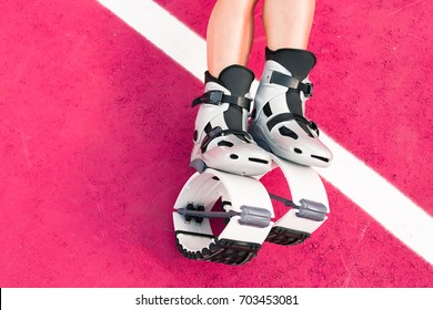Fit legs in kangoo jumping shoes. Beautiful and sexy girl do sport kangoo exercises on pink background and sit
